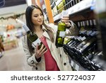 woman deciding what wine to buy ... | Shutterstock . vector #527724037