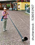 Small photo of Ascona, Switzerland - August 23, 2016: Alphorn player entertain people at the restaurant of Ascona on Lake Maggiore, Ticino canton, in Switzerland.