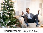 Small photo of Very happy afro-american man can't deal with the emotions, he is very surprised and astonished on the Christmas eve