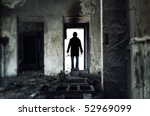 Silhouette on unrecognizable guest in the doorway of the dark industrial interior. Shallow depth of field due to the tilt/shift lens for movie effect. Special colors added - stock photo