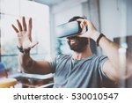 Stock photo young bearded man wearing virtual reality glasses in modern interior design coworking studio 530010547