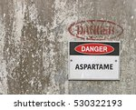 Small photo of red, black and white Danger, Aspartame warning sign