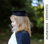 Small photo of Little boy child in black academic gown and squared school hat and bow tie with blonde hair on smiling face standing outdoor on green natural background