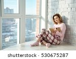 Young Woman Sitting On A Floor...