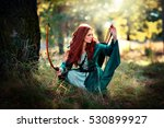 Small photo of Beautiful red haired girl in green medieval dress is going to shoot with arrows and looking afar . Fairy tale story about brave heart woman .Glowing sun on archer. Warm art work.