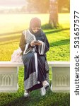 Small photo of Arab women in hijab and abaya reading a message on a smart phone and sitting on the park. The woman is dressed in a black abaya