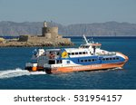 Small photo of RHODES, GREECE - MAY 19, 2010: Ferry leaving the harbor next to the tower and lighthouse of Agio Nikolaos