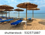 Small photo of Summer morning sea view from Litus beach with sunbeds and strawy sunshades (Sithonia, Chalkidiki, Greece).
