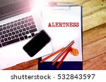 Small photo of ALERTNESS text word in notepad with wooden background, texture and notebookin a table.