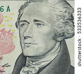 Small photo of Portrait of Alexander Hamilton in front of the Ten dollars bill fragment macro