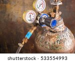 Small photo of Reducer with pressure gauges on the oxygen tank, By attaching a device to prevent the fire back into the tank.Flashback arrestor for regulator ,The safety equipment in the workplace.selective focus.