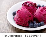 Stock photo plate of blueberry ice cream scoops with fresh berries on wooden table 533649847
