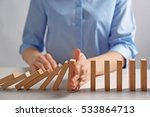 Small photo of Businesswoman hand trying to stop toppling dominoes on table