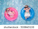 Stock photo two month old twin baby sister and brother sleeping on tiny inflatable pink and blue swim rings 533865133