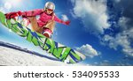 Sports background. Snowboarder jumping through air with deep blue sky in background.