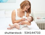 Mother Holding And Feeding Bab...