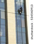 Small photo of Alpinist cleaner working on big height. Cleaning windows in the modern business center.