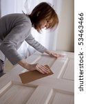 woman sanding door - stock photo