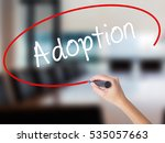 Small photo of Woman Hand Writing Adoption with a marker over transparent board. Isolated on Office. Business concept.