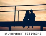couple sitting on wooden bridge ... | Shutterstock . vector #535146343