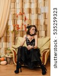 Small photo of Young woman in black with half face skull make-up sitting ion the chair.