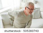 Small photo of people, healthcare and problem concept - unhappy senior man suffering from pain in back or reins at home