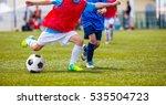 young boys kicking soccer ball...