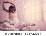 pretty woman sitting on bed and ... | Shutterstock . vector #535723087