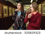 Small photo of Two girl friends standing in a gallery contemplating and discuss paintings artworks displayed on gallery walls