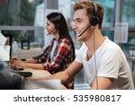 Small photo of Side view of Smiling Coworkers sit by the table in headphones. Call center