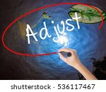 Small photo of Woman Hand Writing Adjust with marker over transparent board. Isolated on nature. Business concept. Stock Photo