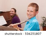 Small photo of boy smiling and learning to play the flute with accompanist