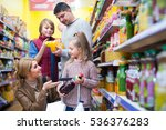 Parents with two kids choosing soda and juice in supermarket