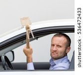 Small photo of Aggressive and violent driver armed with a hoe. Copy space on the gray background.