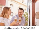 Small photo of Cute couple laughing happily while they are enjoying some beers in the bright sunshine and all eyes on each other