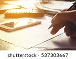 Small photo of Man writing and make note about cost and expenses at office. Finance concept.