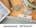 Small photo of IRA file with calculator, pen, coins and glass jar
