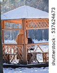 Small photo of Mom with his baby in wooden alcove in snowy park