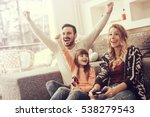 Small photo of Happy family playing video games at home and having fun together.