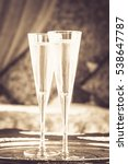 Small photo of Two champagne glasses with oriental canopy bed at the background. Silver tray. Romantic concept. Valentines background. Arabian nights ambiance. Vertical, close up, glasses in the middle, toned