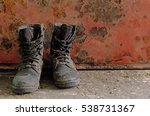 old combat boot on rusty red...
