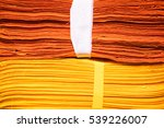 Small photo of Close up of orange and yellow clothes overlapping for background or wallpaper