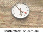 Small photo of White clock on a brick wall with black and red hands at King's Cross St Pancras