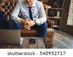 Small photo of Man sitting on couch afore laptop and mobile