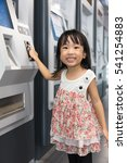 Small photo of Asian Chinese little girl buying admission ticket at MRT station in Kuala Lumpur City, Malaysia.