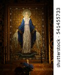 Small photo of September 12, 2015, Mission Dolores Basilica, San Francisco. A mosaic tile altarpiece of an angel with shimmering golden silver halo and wings.