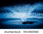Small photo of Aerator,a device for water oxygenation in an artificial pond for breeding fish,blue toned.