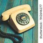 Small photo of Vintage telephone on blue wooden boards. Film colors. Always connected. Remembers loved ones.
