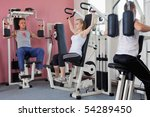 three people exercising on machines at modern gym - health club - stock photo