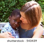 Young caucasian woman holding a beautiful African American child. - stock photo